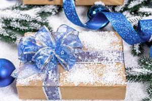 Mit Schnee berieseltes Geschenk in Naturpapier und Blauer Schleife