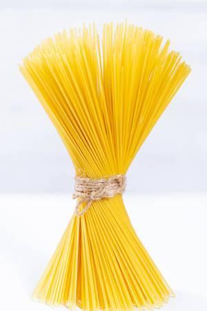 Mit Schnur kunstvoll gebundene Spaghetti vor weißem Hintergrund