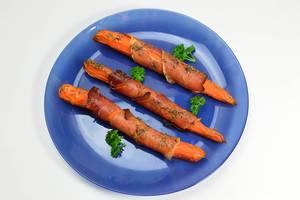 Mit Speck ummantelte, gebackene Karotten auf einem blauen Teller in der Aufsicht