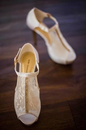 Mit Stickereien besetzte, weiße Brautschuhe mit Absatz auf Holzboden