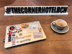 Mit Stickern beklebtes Macbook von Apple neben einer Tasse Kaffee vor dem Hashtag-Schild #TheCornerHotelBCN in Barcelona, Spanien