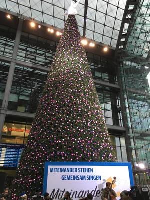 Miteinander stehen, gemeinsam singen im Berliner Hauptbahnhof vor Weihnachtsbaum