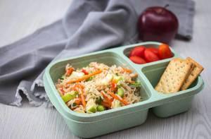 Mittagessen in einer Tupperdose - Reissalat mit Crackern und Tomaten mit einem Apfel im Hintergrund