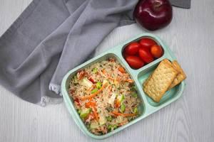 Mittagessen in einer Tupperdose - Reissalat mit Crackern und Tomaten mit einem Apfel in der Aufsicht