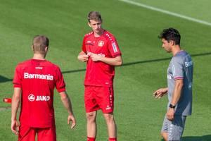 Mittelfeldspieler Lars Bender redet beim Training mit seinen Teamkollegen auf dem Fußballfeld
