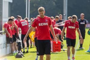 Mittelstürmer Simon Terodde trägt einen kleinen Coca Cola Kasten nach dem Fußballtraining vom Platz