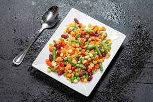 Mix frozen vegetables of different colors in a white plate on a black background. Top view (Flip 2019)