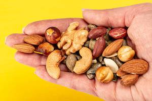 Mix nuts and seeds in a female hand on a yellow background (Flip 2020)
