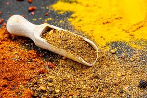 Mix of peppers in a wooden scoop on a background of ground spices
