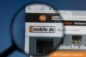 Mobile.de Logo am PC-Monitor, durch eine Lupe fotografiert
