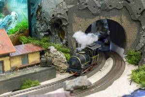 Model railroad. Train going through a tunnel