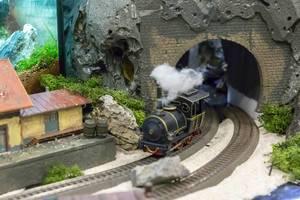 Model railroad. Train going through a tunnel