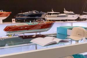 Modell eines luxuriösen Motorboots auf Tisch mit Erklärungsbuch und passendem Hut an Messe