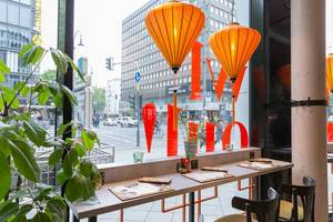 Modern colourful intérieur of the coa Wok & Bowl restaurant in Cologne with plants and seats overlooking the street