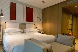 "Modernes Doppelbett-Hotelzimmer des ""The Corner Hotel"" in Barcelona, Spanien, weißen Mauersteinen an der Carrer de Mallorca & Carrer de Muntana"