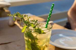 Mojito-Cocktail mit frischen Minzblättern, grünem Strohhalm und Eiswürfeln unter Sonnenschein