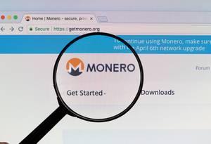 Monero-Logo am PC-Monitor, durch eine Lupe fotografiert