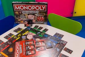 Monopoly Mogeln und Mauscheln ausgepackt auf dem Tisch spielbereit mit Spielkarton im Hintergrund