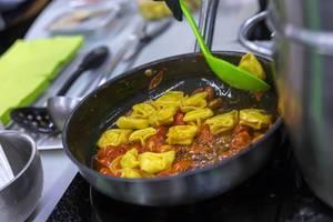 Mosna - frische gefüllte Pasta - vegane Bio Tortellini mit Tomatensoße werden zubereitet