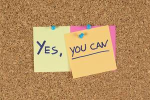 """Motivation slogan """"Yes, you can"""", pinned on a cork wall"""
