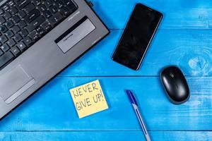 """Motivationszettel mit dem Text """"Never give up"""" - Gib nicht auf - neben einem Laptop, Handy, Stift und Maus"""