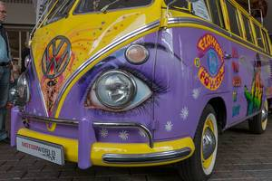 MotorWorld Oldtimer cars at IAA car show in Germany: Colorful retro VW T1 - Bus in new music loving design with Peace-Symbol and rock legend Jimi Hendrix