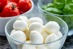 Mozzarella cheese, red cherry tomatoes and fresh Basil leaves in bowls on the table (Flip 2019) (Flip 2019)
