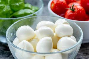Mozzarella cheese, red cherry tomatoes and fresh Basil leaves in bowls on the table