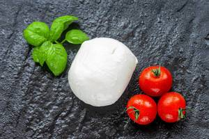 Mozzarella, cherry tomatoes and Basil leaves on black stone background (Flip 2019) (Flip 2019)