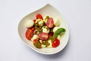 Mozzarella mit Kirschtomaten, Pesto und Basilikum in einer stilvollen Schale