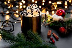 Mug with hot chocolate and marshmallows on a Christmas background with bokeh