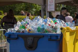 Müllcontainer gefüllt mit leeren PET-Flaschen, Dosen und Plastikbechern am Tomorrowland Festival 2019