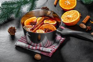 Mulled wine with spices and slices of citrus fruits in a pan