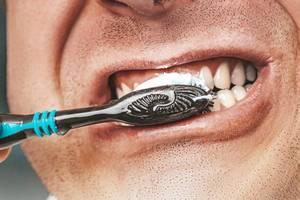 Mundhygiene: Erwachsener Mann putzt seine Zähne mit schwarzer Zahnbürste, in der Nahaufnahme