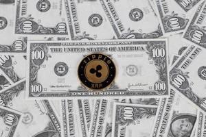 Münze der Kryptowährung ripple (XRP) liegt auf verteilten US-Dollar Noten