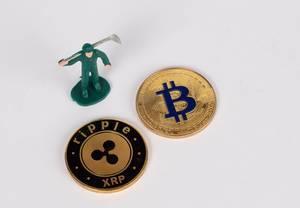 Münzen der Krypto-Währungen ripple (XRP) und Bitcoin mit Minenarbeiter auf weißem Hintergrund