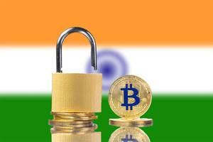 Münzen der Kryptowährung Bitcoin und Vorhängeschloss mit Indiens Flagge im Hintergrund
