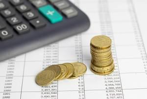 Münzen mit einem Taschenrechner auf einer Tabelle mit Finanzen