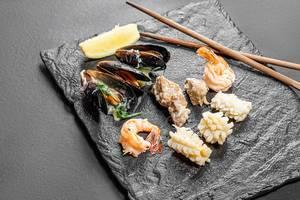 Muscheln, Garnelen und Tintenfisch auf einem schwarzen Teller