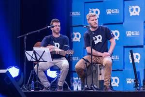 Musiker schauen aufmerksam einem Redner zu