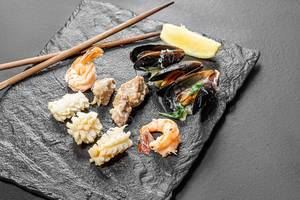 Mussels, shrimp, squid and fish on a black stone background (Flip 2019)