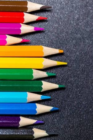 Nach Farben sortierte Buntstifte auf schwarzem Untergrund