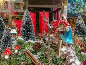Nachstellung des Märchens Rotkäppchen, Wolf schleicht sich als Großmutter verkleidet an Rotkäppchen, die im verschneiten Wald zwischen Tannenbäumen und Pilzen steht, im Hintergrund vier rote Kerzen und Weihnachtsdekoration in Schaufenster
