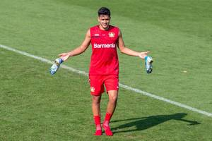 Nadiem Amiri in red Barmenia football jersey, posing and walking barefoot with his blue football shoes in his hands