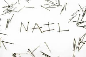 Nägel verteilt auf weißem Hintergrund und bilden das Wort NAIL