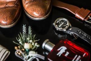 Nahaufnahme Accessoires des Bräutigams wie Uhr, Ansteckstrauß, Parfum, Gürtel und Schuhe