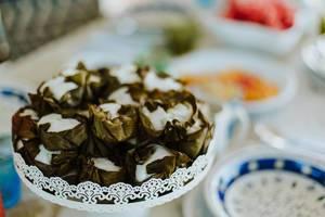 Nahaufnahme asiatische Reisküchlein umwickelt mit Bananenblättern im Fokus vor Frühstücksbuffet