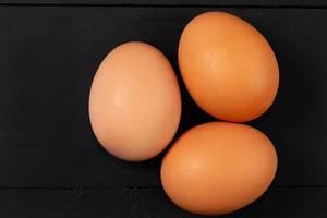 Nahaufnahme auf drei Hühnereien auf dem schwarzen Hintergrund