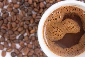 Nahaufnahme Blick von oben auf dampfende Tasse mit Kaffee auf Kaffeebohnen auf weißem Tisch