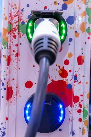 Nahaufnahme bunte Ladestation mit beleuchteten Steckdosen für Elektrofahrzeuge